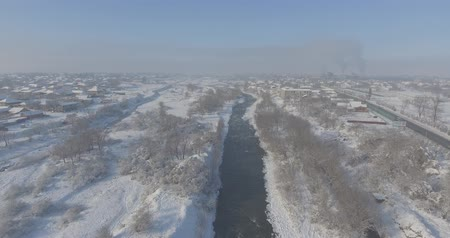 Aerial view village in the winter. Beautiful landscape of frosty morning. The bird flies