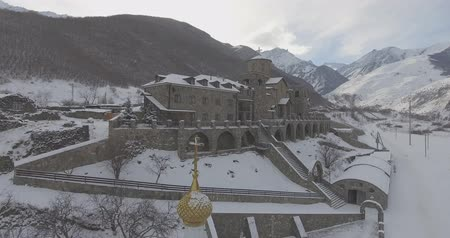 Flying on a drone over a monastery in the mountains in winter. On the background of a beautiful panorama of snow-capped mountains