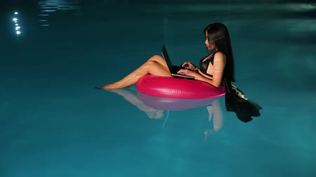 Young beautiful brunette woman working on laptop in the pool