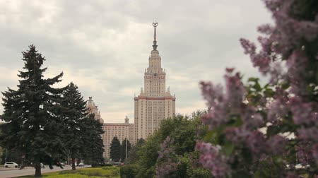 stalinist : Main building of Moscow State University (also known as MGU) behind lilac bushes on a cloudy day.