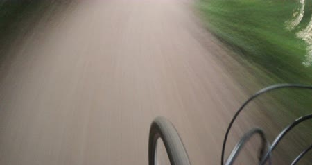 diminishing : Hyper laps footage of driving on a dirt road in the park on bike at summer. The rotation of the wheel in the foreground Stock Footage
