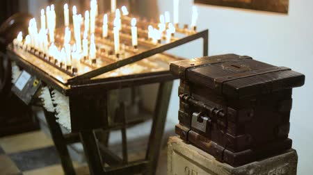 offertory : donation box near burning candles in a church