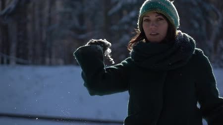 kavga : Slow-mo footage. Beautiful young girl throwing snowball at camera