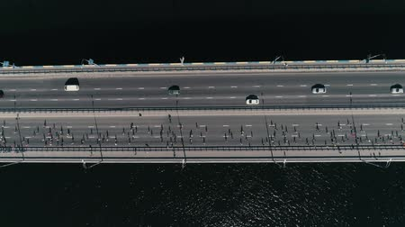 vertical : 4K Aerial drone fooage. Marathon running on the bridge. Horizontal movement dolly shot top view