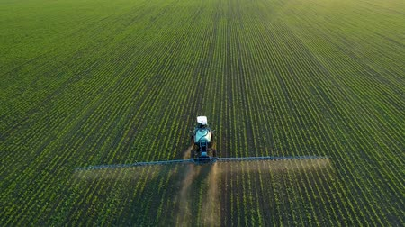 herbicides : 4K aerial drone footage. Following tractor sprayer on soybean fields