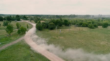 ladění : Aerial Drone footage. Fly over abandoned farm to rally car on road