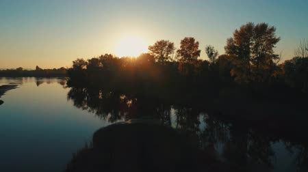 enviroment : Aerial drone footage. Flight over calm river at sunset