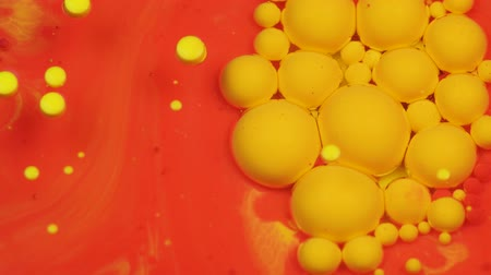 молекула : Amazing red and yellow bubbles of paint on the oil surface. Paint in oil. Стоковые видеозаписи
