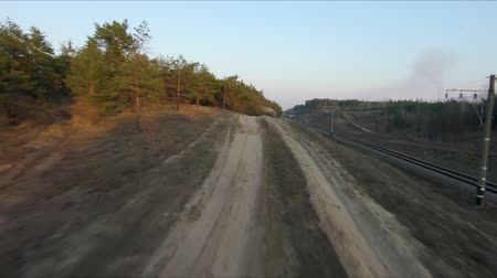 quad bike : Drone racing view. Fly over dust road in forest at sunset. Dynamic shot