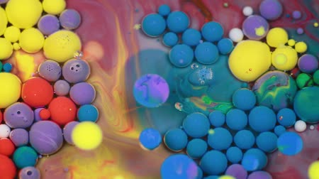 yellow ink cloud : Abstract multicolored bubbles paint. Slow motion. Top view Stock Footage