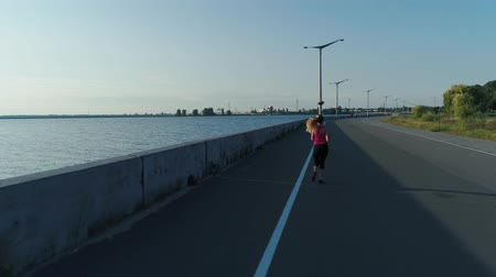 townsman : Aerial shot. Woman is running in morning time in embankment of sea town. Stock Footage