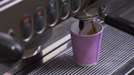 grãos de café : Coffee machine making double espresso in paper cup.