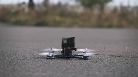 kontrolovány : FPV racing drone takes off from the asphalt surface