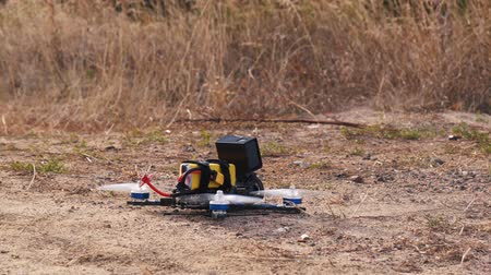 kontrolovány : FPV racing drone takes off from a dirt surface raising dust and stones
