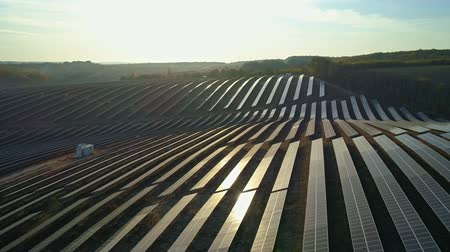fotovoltaica : Aerial drone footage. Low flight above solar panel farm at sunset autumn season.