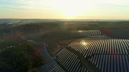 fotovoltaica : Aerial drone footage. Radial flight over solar panel farm at sunset autumn season. Vídeos