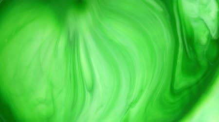 акварель : 4K footage. Ink in water. Green ink reacting in water creating abstract background.