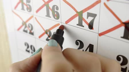 memo : Female hand crosses with red marker the calendar day 24. Slow motion shot. Close up