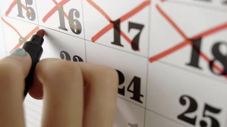 měsíčně : Female hand crosses with red marker the calendar day 23. Slow motion shot. Close up