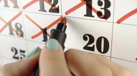 excluir : Female hand crosses with red marker the calendar day 20. Slow motion shot. Close up