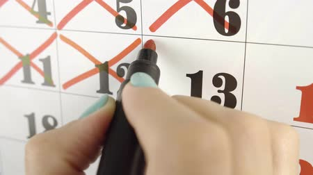 hónapokban : Female hand crosses with red marker the calendar day 13. Slow motion shot. Close up
