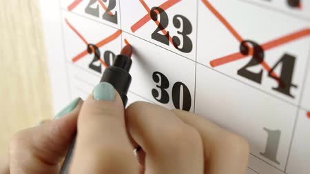 excluir : Female hand crosses with red marker the calendar day 30. Slow motion shot. Close up Stock Footage