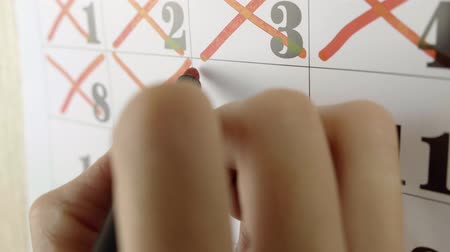 měsíčně : Female hand crosses with red marker the calendar day 10. Slow motion shot. Close up
