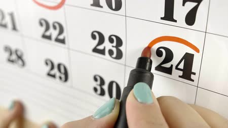 excluir : Female hand encircles with red marker the calendar day 24. Slow motion shot. Close up Stock Footage
