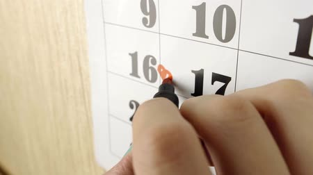 excluir : Female hand note birth day with red marker the calendar day 17. Slow motion shot. Close up Stock Footage