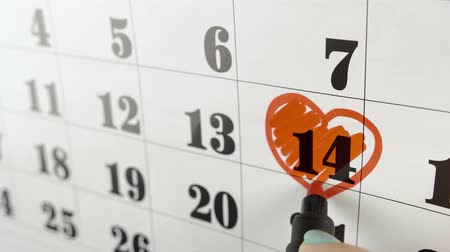 memo : Saint valentine day. draws heart around with red marker the calendar day 14 February. Slow motion shot. Close up Stock Footage