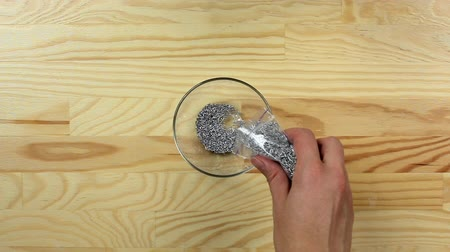 kobliha : Woman pours silver sugar sprinkles dots into a glass bowl, top view