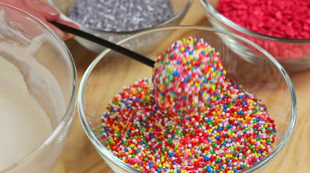 kaynatmak : A woman sprinkles cake pops with colored dressing, close up