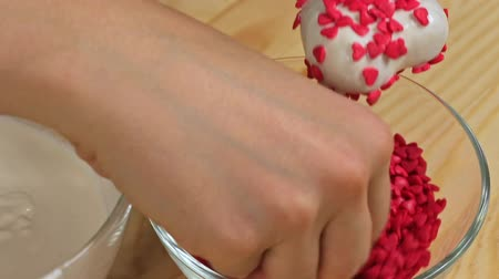 batatas : A woman sprinkles heart cake pops with red dressing, close up Stock Footage