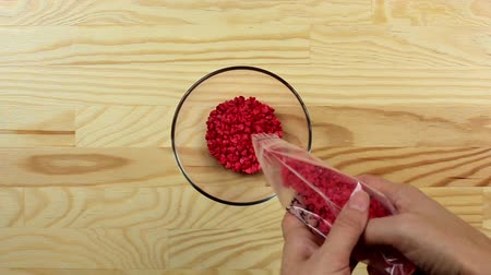 aparelho : Woman pours sugar hearts sprinkles dots into a glass bowl, top view Stock Footage