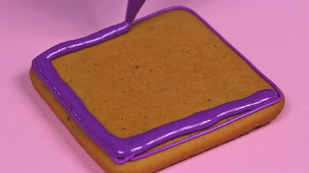 anason : Applying violet glaze to ginger biscuits, close-up