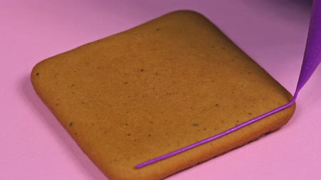Applying violet glaze to ginger biscuits, close-up