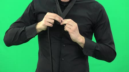 descontraído : The guy in the black shirt is tying a black tie on green screen