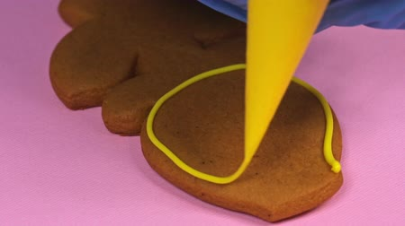 украшенный : Applying yellow glaze to ginger biscuits, close-up