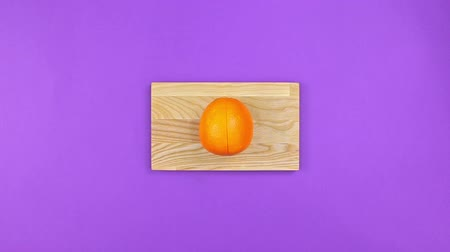 vitamina : Self cuts orange on board on purple background, top view Stock Footage