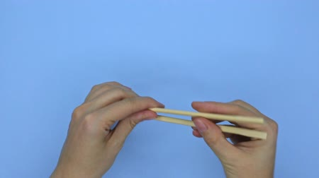 rulolar : Problems beginner with chopsticks, top view on blue background Stok Video