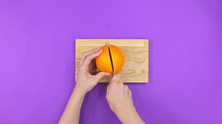 vitamina : Girl cuts orange on board on purple background, top view Stock Footage