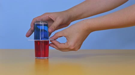 Physical experiment, coloring water in glasses and mixing