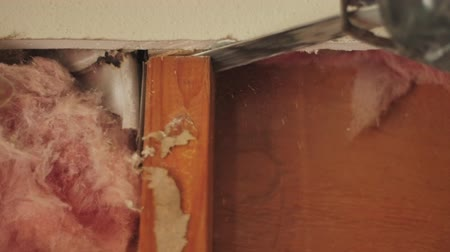 a slow motion shot of a carpenter with a saw cutting along some wood framing