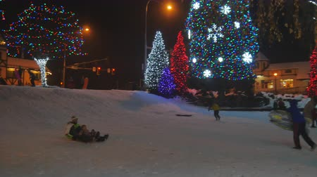 boŻe narodzenie : a bunch of kids playing in the snow on sleds in a beautifully lit christmas town center