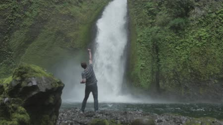 peak : an excited man jumping in front of a waterfall. hes excited to see the waterfall Stock Footage