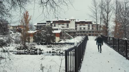 a person walking on a snowy bridge over a river in a german town