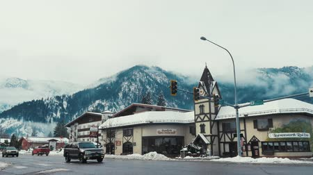 a small town filled with people, cars and snow.