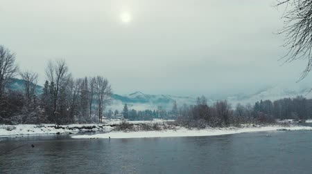 a scene with snowy mountains, a river and snow fall with the sun peaking behind the clouds Dostupné videozáznamy