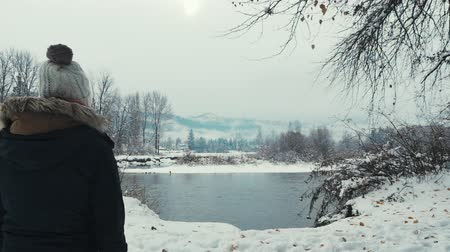 a girl walking into a scene with snowy mountains, a river and snow fall Dostupné videozáznamy