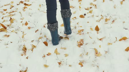 a girl with cute boots walking in snow in slow motion
